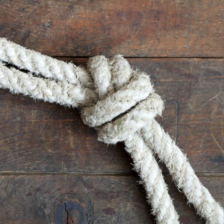 Two old ropes constrained with knots lying on wooden background