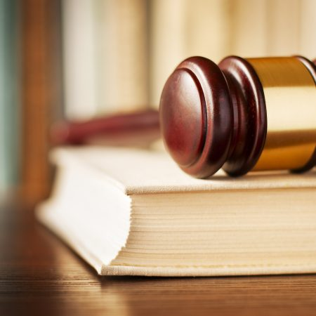 Conceptual image of law enforcement, justice and sentencing with a closeup view of a wooden judges gavel lying on a law book